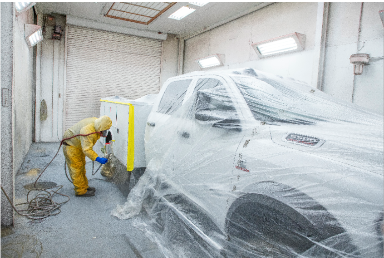 Person painting vehicle with sprayer